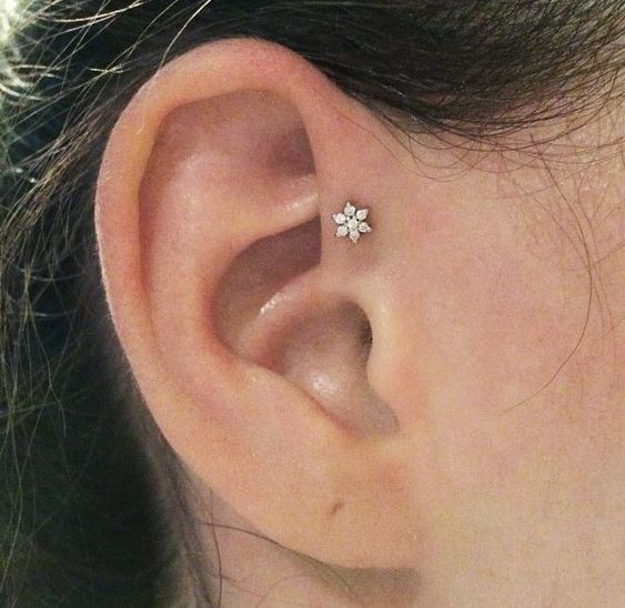 a single ear piercing - a forward helix one done with a chic floral stud