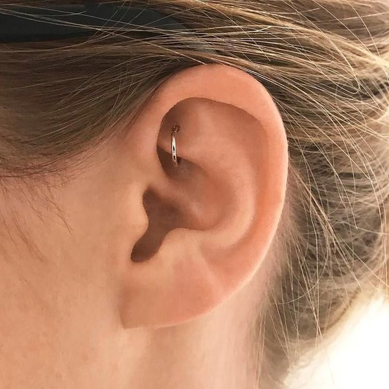 a single ear piercing   a rook one with a silver hoop is a stylish and minimalist idea to rock