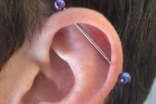 a single industrial piercing done with a bar with shiny purple beads is a bold and creative idea