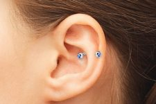 a single snug piercing with a blue rhinestone earring is a bold and catchy idea to try