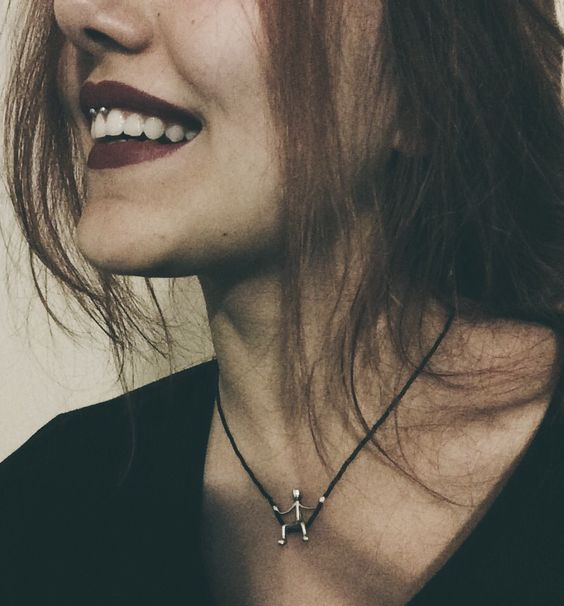 a smiley piercing done with a barbell jewelry piece plus a dark lip for a bold look