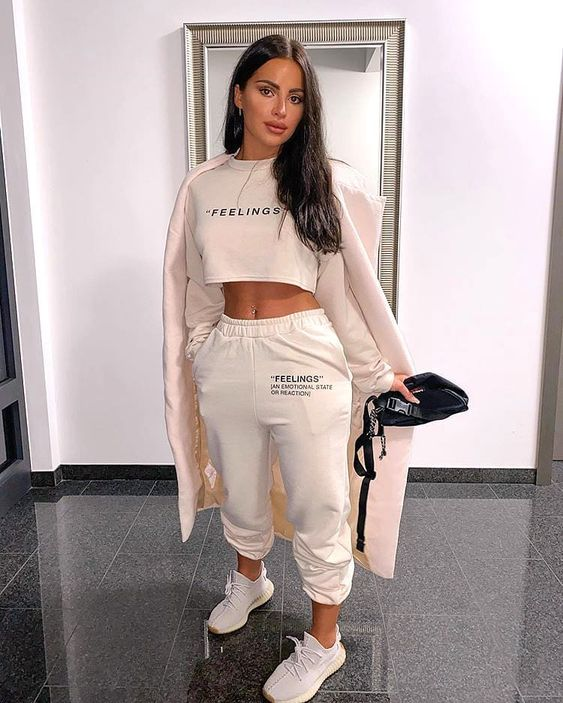 a sporty outfit with a white cropped sweatshirt, joggers, white trainers, a blush coat and a black bag