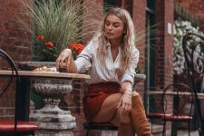 a striped shirt, a red suede mini, rust-colored knee high boots for a chic fall look