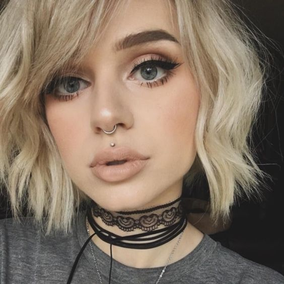 a stud medusa piercing paired with a ring in the septum for a bold and edgy look