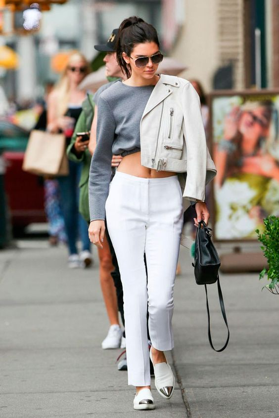 a stylish outfit with a grey cropped sweatshirt, white pants, a white cropped leather jacket and white and silver flat shoes