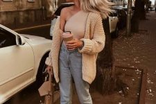 a tan one shoulder top, light blue jeans, tan flat shoes and a bag plus a neutral chunky knit cardigan