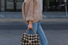 a tan oversized chunky knit sweater, blue raw hem jeans, snakeskin mules and a cozy bag