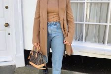 a tan turtleneck, blue jeans, black combat boots, a brown bag and a tan oversized blazer