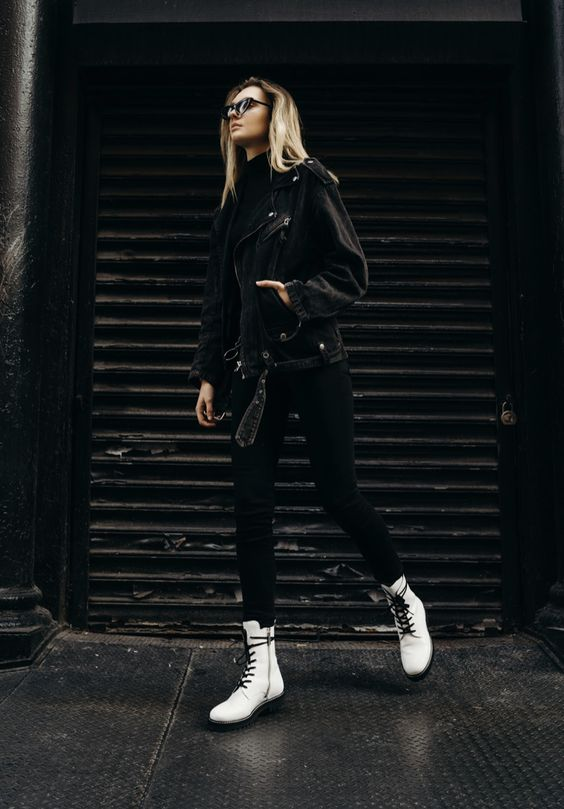 a total black look with a sweater, skinnies, a denim moto jacket refreshed with white combat boots