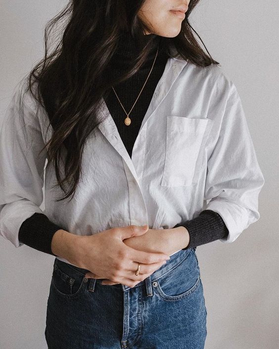 a trendy casual look with a black turtleneck, a white shirt, blue jeans and a necklace