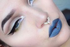 a vertical labret piercing plus a septum piercing with a shiny embellished ring for a bold look