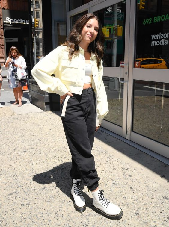 a white crop top, black cargo pants, white combat boots, a yellow shirt jacket for the fall
