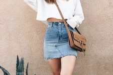 a white cropped sweatshirt, a blue denim mini, black sneakers and a brown bag