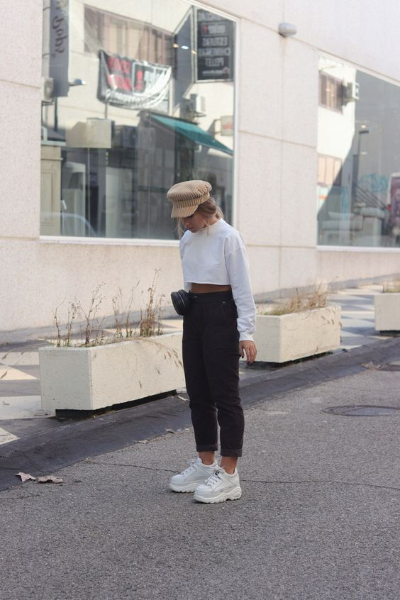a white cropped sweatshirt, black jeans, white trainers, a black waist bag and a cap