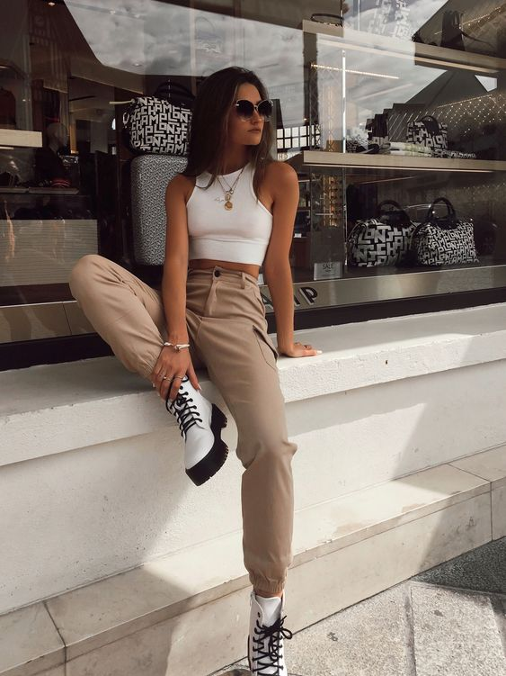 a white halter neckline crop top, tan cargo pants, white combat boots and layered necklaces