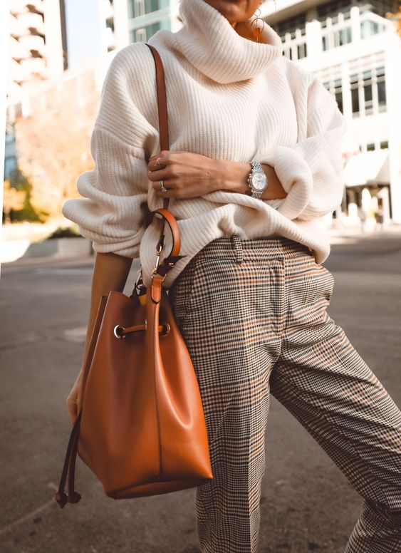 a white oversized chunky knit sweater, plaid pants, an amber bag are a comfy work outfit
