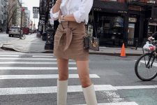 a white shirt, a brown bow mini skirt, white knee high boots and a dark printed bag
