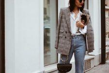 a white shirt, a plaid blazer, blue raw hem mom jeans, burgundy sock boots and a bag with a round handle