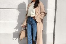 a white top, blue jeans, tan striped shoes, a tan duster and a tan bag for a chic work look