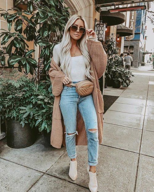 a white top, blue ripped jeans, blush booties, a tan chunky knit cardigan and a waist bag