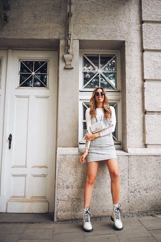 a white top with lace up sleeves, a grey plaid mini dress, white combat boots and a white mini bag