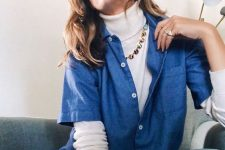 a white turtleneck, a bright necklace, a blue shirt and jeans for a casual and chic look