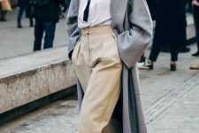 a winter look with a black turtleneck, a white shirt, tan pants and lace up booties plus a grey coat