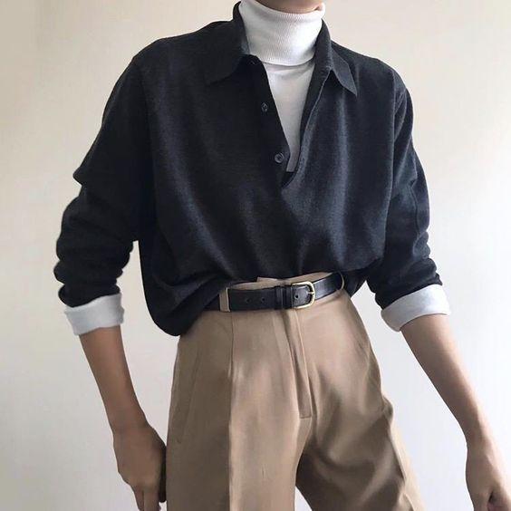 an office look with a white turtleneck, an oversized black shirt, tan pants and a black leather belt