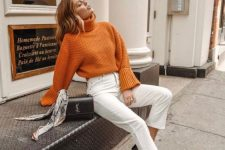 an orange chunky knit sweater with a high collar, white jeans, twon tone shoes and a black bag
