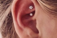 an oversized diamond stud and a little shiny star and stud rook piercing