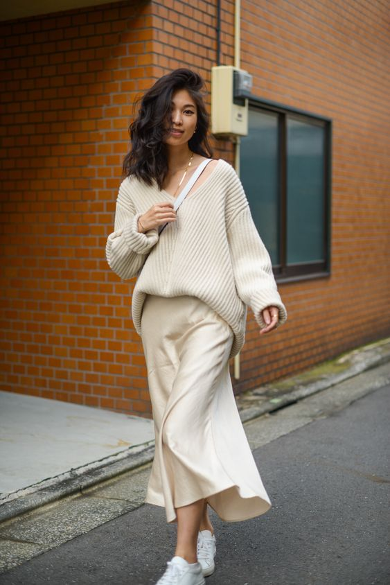an oversized white ribbed sweater, a midi slip skirt, white sneakers and a bag