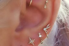 bright and chic ear styling with lots of celestial earrings including a rook piercing with a hoop