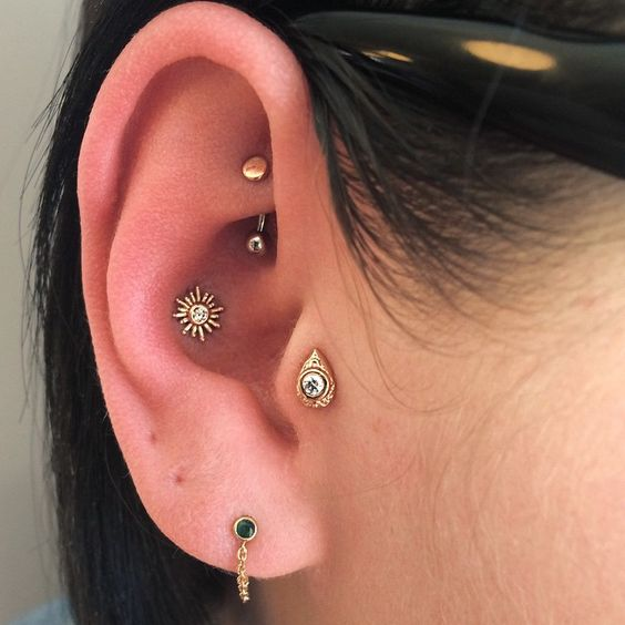 catchy and bold ear piercings - lobe, conch, tragus and rook ones styled with unique studs