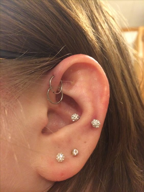hoops in forward helix, shiny stubs in the lobe and a shiny earring in the snug are bold and glam