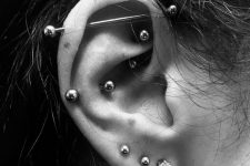 layered piercings – lobe, snug, rook ones with matching earrings and an industrial with a matching bar