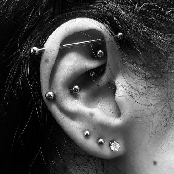 layered piercings - lobe, snug, rook ones with matching earrings and an industrial with a matching bar