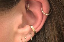 multiple layered piercings including a delicate gold diamond hoop in the rook look chic