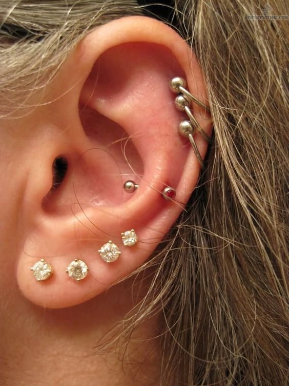 multiple lobe piercings with matching studs and a snug piercing with a red rhinestone earring