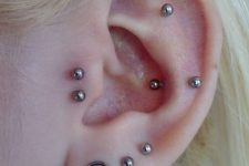 multiple piercings – in the forward helix, tragus, lobe, flat and snug with matching studs