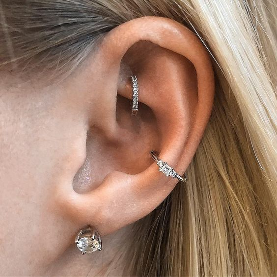 stylish ear piercings done with diamond studs and hoops including a shiny hoop in the rook