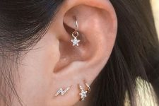 stylish gold and diamond studs in piercings and a cool hoop with a star in the rook