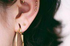 stylish piercings – a large hoop, shiny gold studs in the helix and a gold hoop in the rook