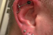three lobe piercings plus an industrial one with a bold bar with a rhinestone and a circle