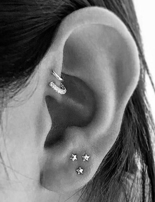 three tiny star studs in the lobe and two embellished hoops in the forward helix