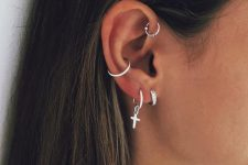 two silver earrings in the lobe, a conch hoop and a mini hoop in the forward helix
