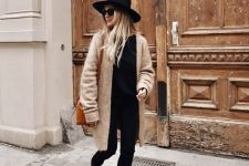 05 a stylish fall look with a black tee, jeans, booties, a tan cardigan, an amber bag and a black hat