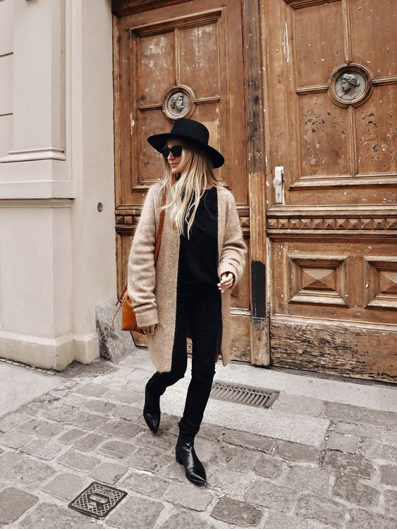 a stylish fall look with a black tee, jeans, booties, a tan cardigan, an amber bag and a black hat