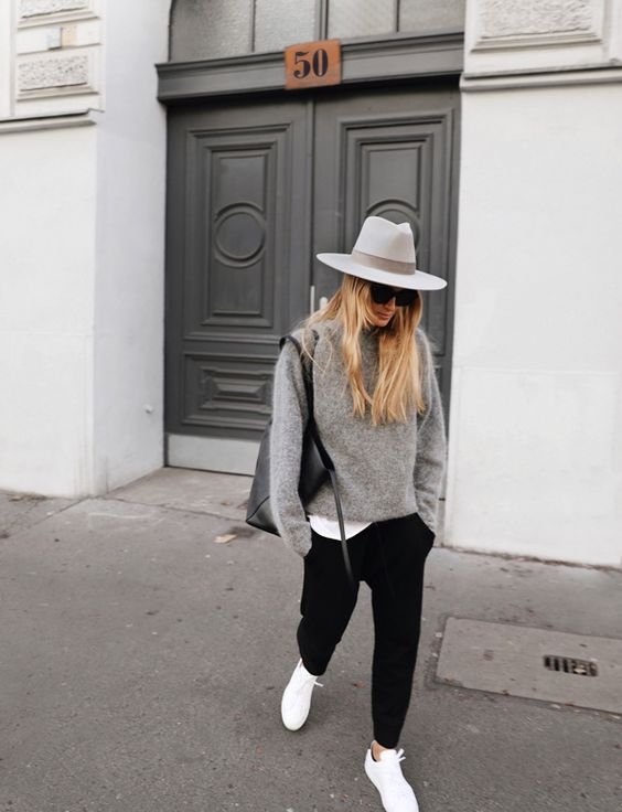 a white tee, black pants, a grey cashmere sweater, white sneakers and a white wide-brim hat