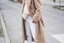 09 a neutral winter outfit with white jeans and a sweater, tan sneakers, a tan fur coat, a neutral bag and a tan beanie