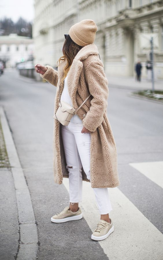 a neutral winter outfit with white jeans and a sweater, tan sneakers, a tan fur coat, a neutral bag and a tan beanie
